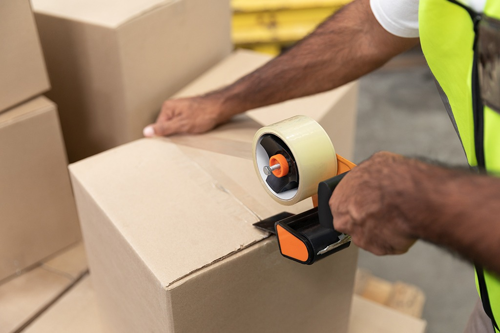 warehouse packing operations with a worker packing a parcel with a tape gun